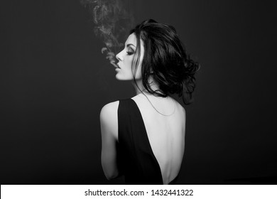 Fashion beauty makeup cosmetics brunette woman smokes on dark background in black dress, white smoke from her mouth. Erotic girls, black and white