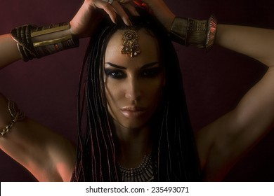 Fashion Beauty. Mystic Make-up. Beautiful Womans With Luxury glossy gold Makeup and stylish hair (dreadlocks) . Beautiful sensitive Girl Face, accessories