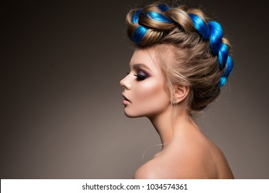 Fashion beauty portrait of a beautiful girl with bright creative make-up and blue hair.