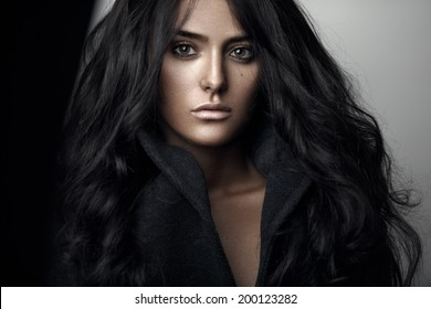 Fashion beauty portrait of beautiful sensual brunette girl with curly long black hair.