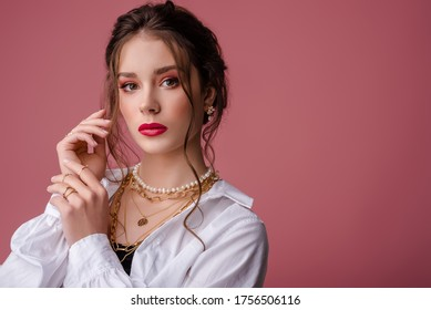 Fashion, beauty portrait of elegant woman wearing trendy jewelry: river pearl earrings, necklace, chains, many golden rings. Model with bold color makeup, posing on pink background. Copy, empty space