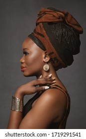 fashion beauty portrait of a lovely young black woman wearing an African cotton dress with a turban and ethnic jewelry on a black studio background