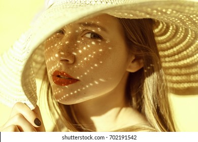 Fashion beauty portrait of a woman in a hat, a shadow falls on a woman from a hat and looking at camera. Yellow background, outdoor