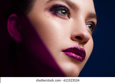 Fashion Beauty Portrait of a young attractive women. Colourful makeup with red lips.