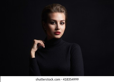 fashion beauty portrait of a young woman in a black roll neck jumper. beautiful girl with short hair.mole on her face
