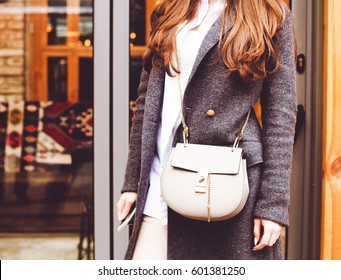 Fashion and Beauty. The redhead fashionable girl is holding a fashionable small handbag in hand. Close-up, street-style. Part of the body. Outdoor. Fashion blogger.