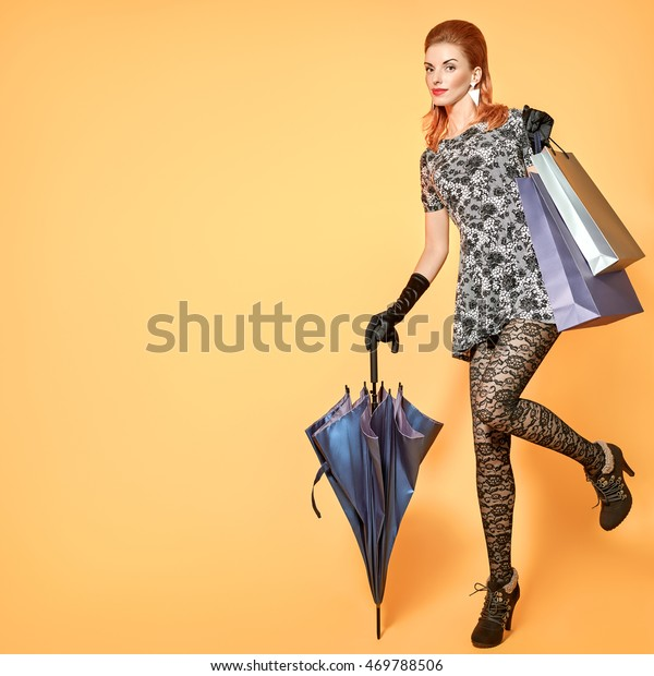 a229b2aa Fashion beauty sexy woman with shopping bags, umbrella, stylish accessories.  Elegant luxury Lady