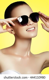 Fashion & beauty. Sexy woman in swimsuit with golden sunglasses. Shot of a beautiful model in white bikini and dark sunglasses. Young girl posing in white swimsuit and sunglasses on yellow background