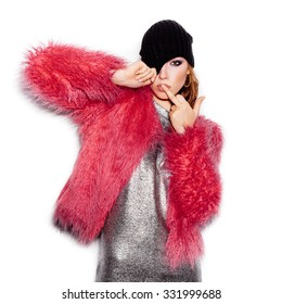 Fashion Beauty Swag Girl wearing silver dress, pink fur coat, black beanie hat. Stylish Haircut and Makeup. Gorgeous young Woman kissing middle finger on white background no isolated