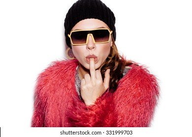 Fashion Beauty Swag Girl wearing silver dress, pink fur coat, black beanie hat. Stylish Haircut and Makeup. Young sexy Woman sucking middle finger on white background no isolated