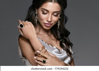 Fashion And Beauty. Woman With Makeup In Jewelry. Portrait Of Sexy Young Female With Stylish Hairstyle Wearing Beautiful Accessories Such As Diamond Earrings, Gold Bracelets And Rings. High Quality