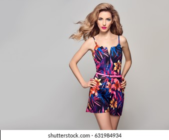 Fashion Beauty woman in Trendy Summer Dress. Stylish wavy hairstyle, Makeup, Summer Floral Outfit. Glamour Blond Model in Sexy Jumpsuit. Playful Girl, Luxury fashionable Accessories