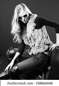 Fashion beauty young woman in sunglasses sitting chair in studio, black and white