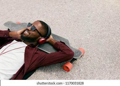Fashion. Black Man Listening Music In Headphones On Street