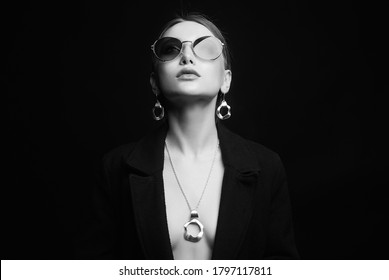 fashion black and white portrait of Beautiful sexy woman in jewelry and sunglasses. sexual woman over black background