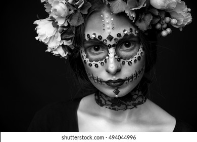 Fashion black and white portrait of a beautiful Halloween model with creative make up,  rhinestones and wreath of flowers on black background