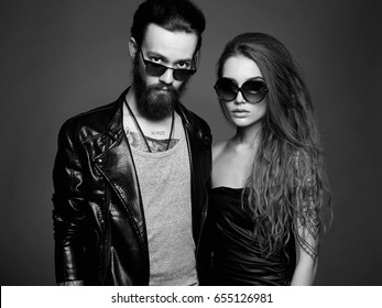 fashion black and white portrait of beautiful couple in sunglasses.bearded Hipster boy and beauty girl