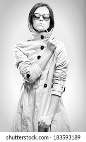 Fashion black and white portrait of fashionable woman in white coat with sunglasses and cigarette