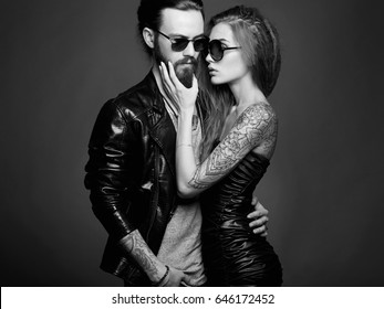 fashion black and white portrait of lovely beautiful couple in sunglasses.bearded Hipster boy and beauty girl with tattoo