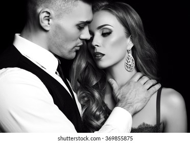 fashion black and white studio photo of beautiful couple in elegant clothes, gorgeous woman with long blond hair embracing handsome brunette man
