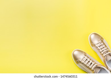 Fashion, blog, blogging, lifestyle, well-being trendy concept. Pair of golden female sneakers on yellow background, top view, copy space, flat lay