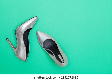 Fashion blog concept. bright silver women high heel shoes on mint green background. Flat lay, top view trendy beauty female background.