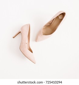 Fashion blog concept. Pale pink women high heel shoes on white background. Flat lay, top view trendy beauty female background.