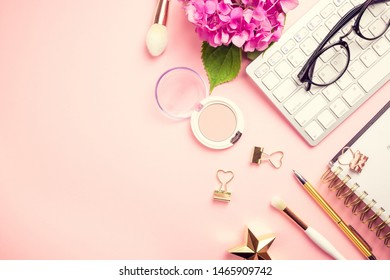 Fashion blog, home office desk. Female workspace with laptop, pink hydrangea, golden accessories, pink diary on pink background. Top view. Copy space