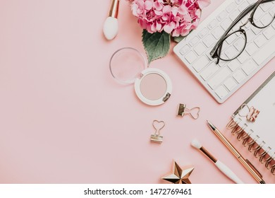 Fashion blog, home office desk. Female workspace with laptop, pink hydrangea, golden accessories, pink diary on pink background. Top view. Copy space. Toned images