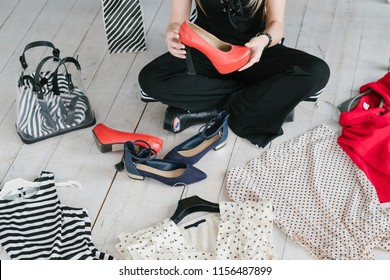 fashion blogger conducting a review of new fashionable apparel and accessories collection. woman holding red high heel shoes. clothing items scattered on the floor.