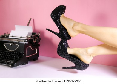 Fashion blogger minimal pink creative concept with typewriter and woman slim legs wearing high heels. Retro typewriter. Fetish shoes.