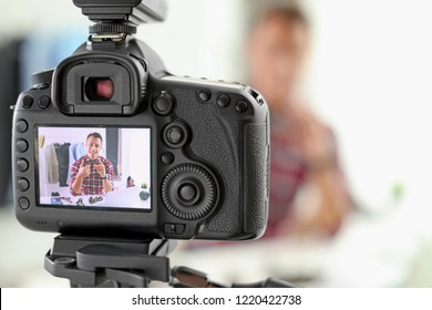 Fashion blogger recording video indoors, focus on camera display. Space for text