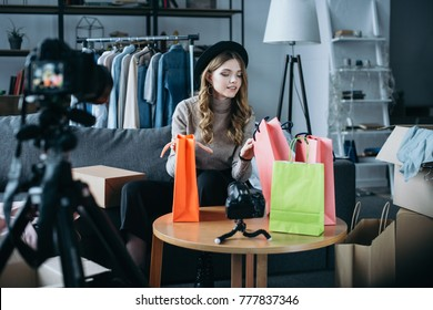 fashion blogger sitting with shopping bags and recording new video for vlog