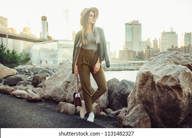 Fashion blogger woman posing in New York City wearing new summer casual outfit with hat, pants and leather bag