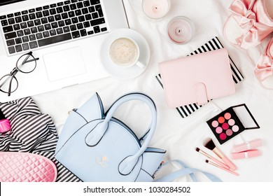 Fashion blogger workspace with laptop and woman accessory in bed. flat lay,  top view
