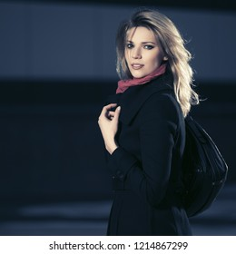 Fashion blond business woman with leather handbag walking in city street Stylish female model wearing classic black coat and pink scarf