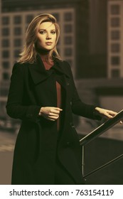 Fashion blond business woman walking in a city street. Stylish female model in classic black coat outdoor