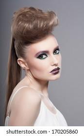 Fashion Blond Model Portrait. Hairstyle. Haircut. Professional Makeup. Unusual creative makeup. Closeup portrait. Studio shot.