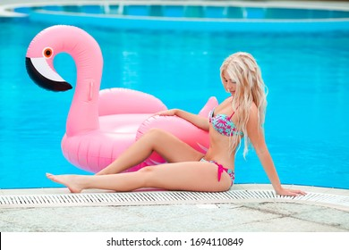 Fashion blond model woman in white bikini posing on Pink inflatable flamingo by swimming pool ring, tube, float. Summer vacation holiday luxurious resort.