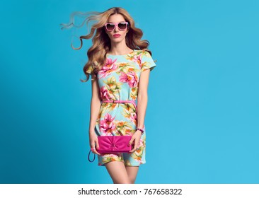 Fashion. Blond Woman. Young beauty Lady in Floral Dress Blowing lips. Trendy Hairstyle, Glamour Pink Clutch. Playful Girl, Spring Summer Outfit