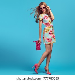 Fashion. Blond Woman. Young beauty Lady in Floral Dress, Trendy Hairstyle, Pink Heels, Glamour Clutch. Playful shapely fashionable Girl, Spring Summer Outfit