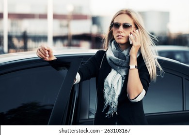 Fashion blonde business woman in sunglasses calling on cell phone leaning on car door Stylish model in black blazer and gray scarf