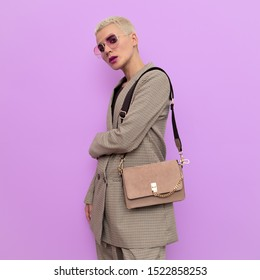 Fashion blonde model in a checkered vintage suit and stylish accessories