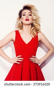 Fashion blonde model in sexy red dress in the studio. Beauty portrait photo