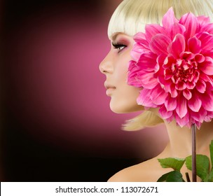 Fashion Blonde Woman with Dahlia Flower. Blond Hair. Hairstyle. Haircut. Makeup