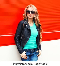 Fashion blonde woman in sunglasses black rock jacket at city over red background