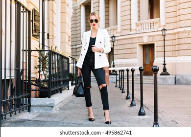 Fashion blonde woman in sunglasses is walking on street on high heels. She wears white jacket and black ripped jeans