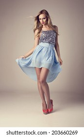 fashion blonde woman wearing ethereal skirt, glitter top and high heels
