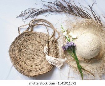 Fashion boho style. Straw, palm trendy round bag on white background. Summer vacation and travel concept. Women's beach bohemian accessories. Top view.