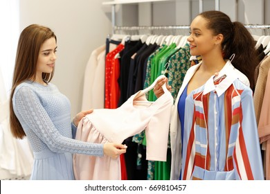 Fashion boutique owner young African woman holding two dresses for her female client to buy. Attractive young woman choosing a new dress at the clothing store with the help of a shop assistant